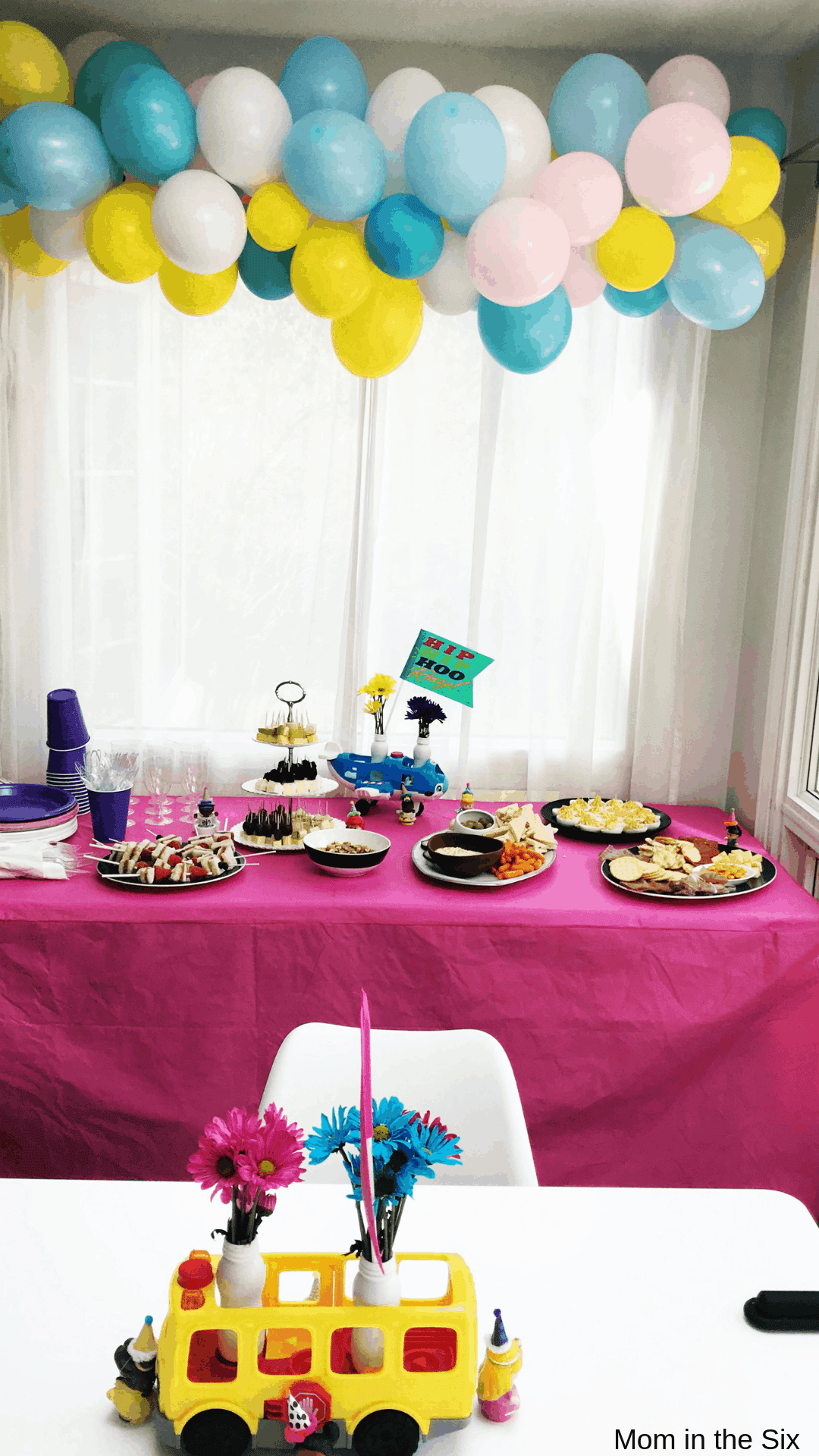 Balloon banner above table with food and Little People Bus center piece