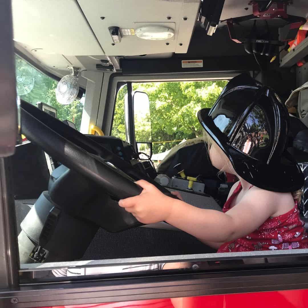 kid sitting in a firetruck