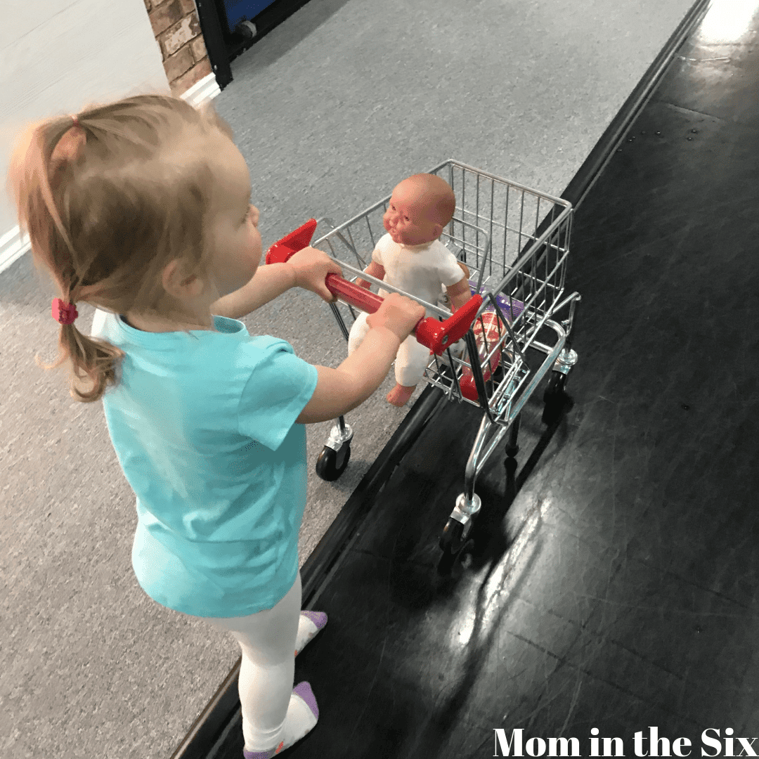 toddler at an indoor playground pushing a pretend shopping cart with a doll in it