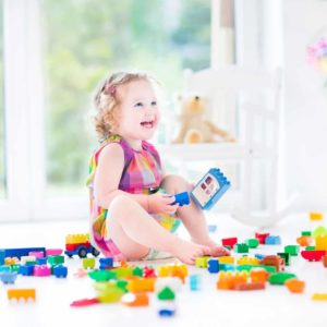 toddler girl smiling in a pile of toys