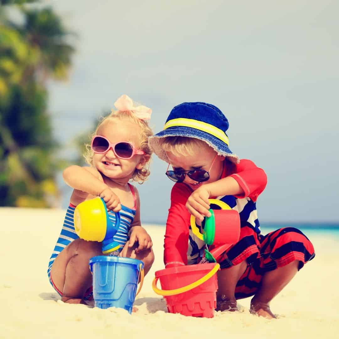 two toddlers playing in the sand at the beach