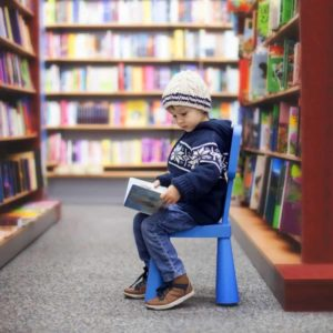 toddler sitting on a chair reading a book at a library